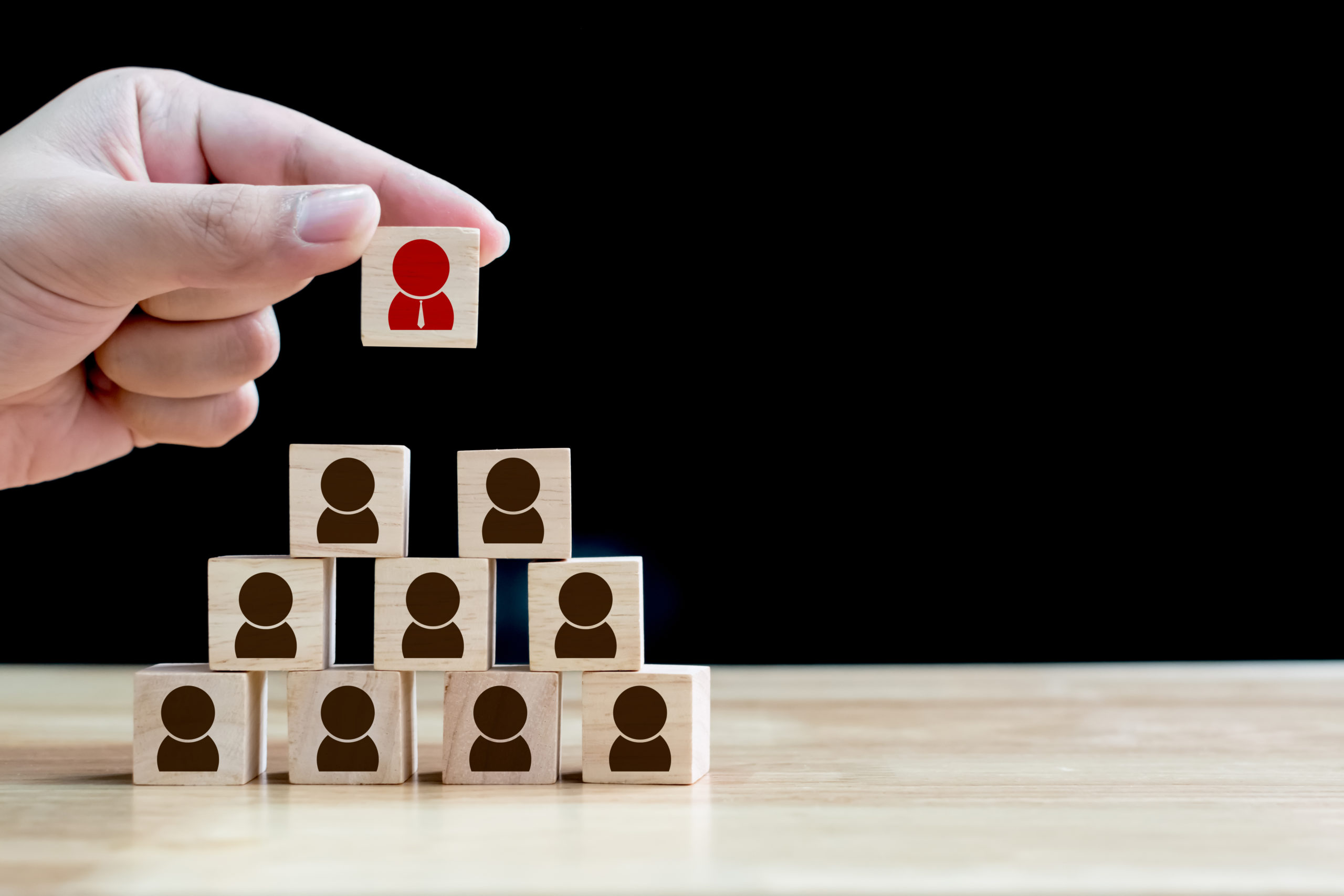 A tower of small wooden blocks with silhouettes of employees.